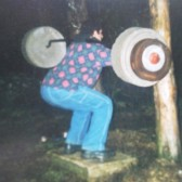 Joe Kinney squats on his self made safety squat bar. The plates were cement which he also made.